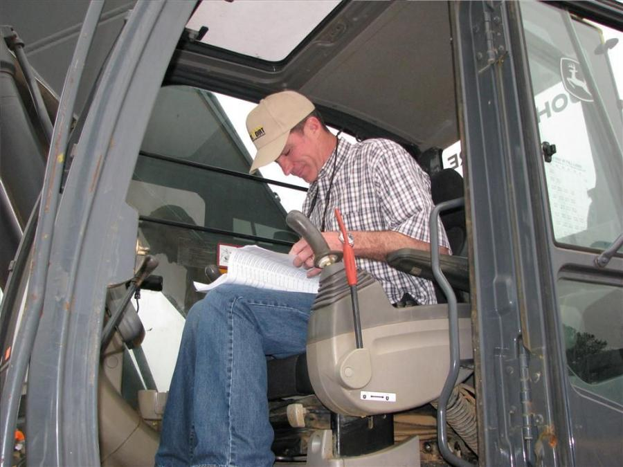 Brett Johnson of Vertical Earth, Cumming, Ga., reads the buyer's guide while sitting in the cab of this John Deere excavator.