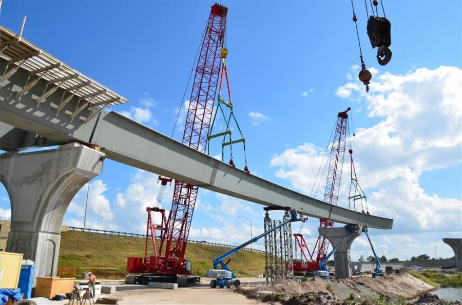 Cranes lift a steel tub girder into place.