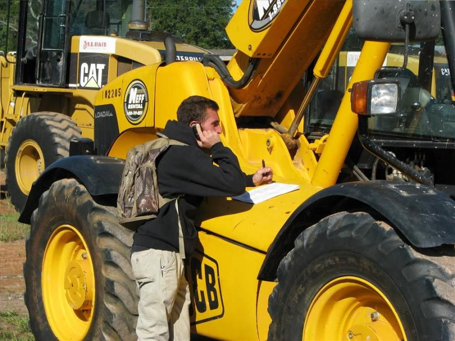 Phoning his office in New York while jotting some notes on a JCB Loadall of interest is Mike Montano of Montano Equipment Sales and Rentals, Saugerties, N.Y.
