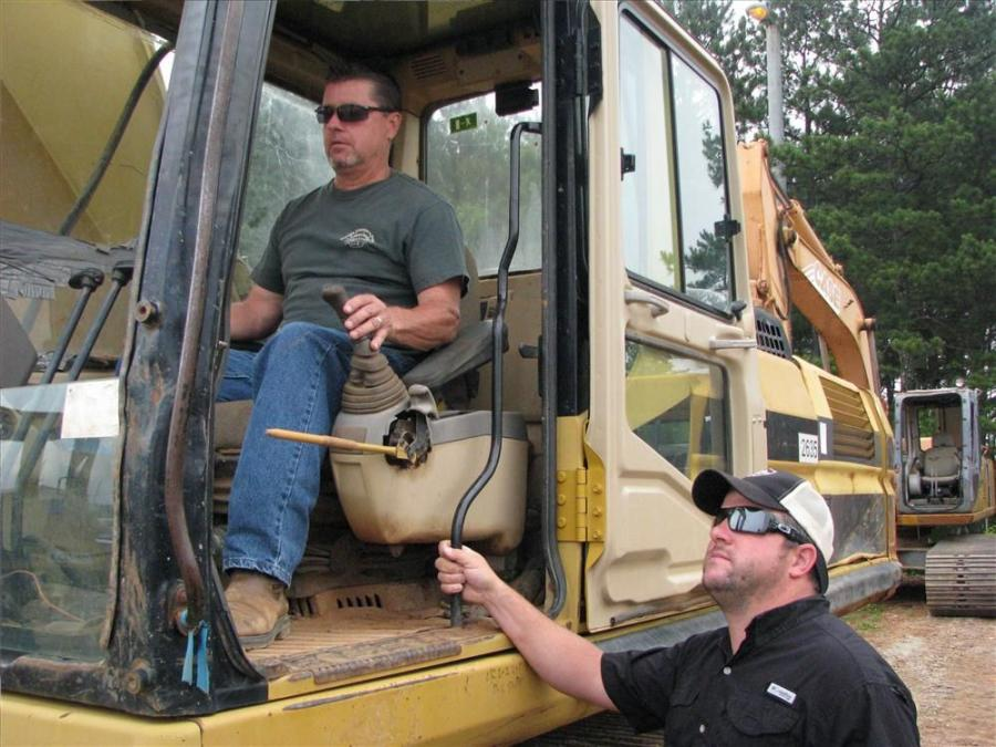 Jim Aldridge (L) and Brandon Webb, both of McClellan & Webb Contracting, Dallas, Ga., test out a Cat 330L excavator in the sale line up.