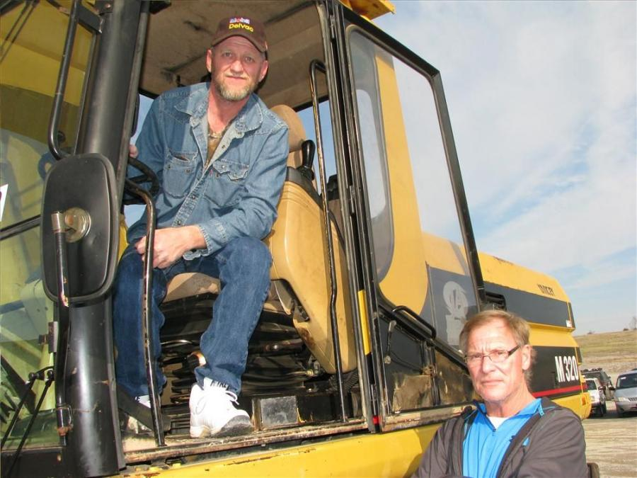 James Berg (L) and Ralph Travis, owner of B&B Dredging & Excavating Co., Waverly, Tenn., inspect a  Cat M320 wheeled excavator they are interested in.