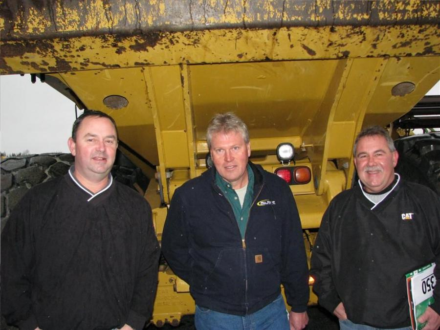 Seeking shelter from the rain under the bed of a Cat 740 artic truck (L-R) are Moe Pratt and Bill Miller, Bill Miller Equipment Sales, Eckhart, Md.; and John Alexander, Alban CAT, Baltimore, Md.