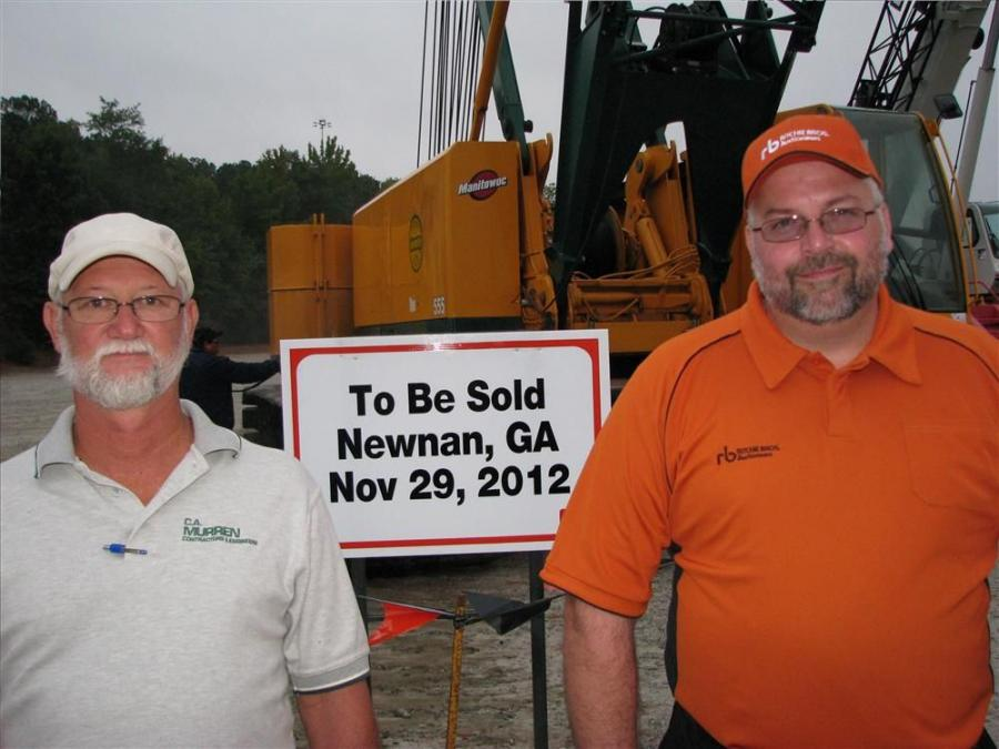 A hint of things to come. Perry Taggart (L),  C.A. Murren Contractors & Engineers, Grayson, Ga., and his Ritchie Bros. representative Alex Wood stand in front of a nice package of C.A. Murren machines, including a Manitowoc 555, which will go on the aucti