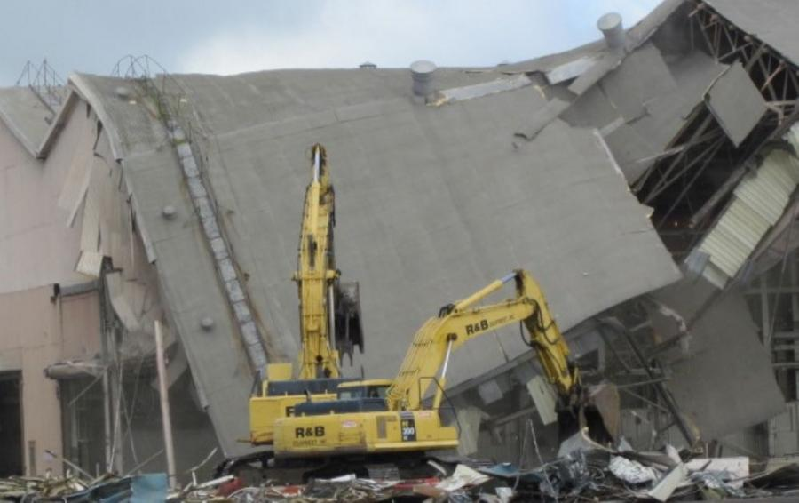 Excavators help tear down part of the roof of the former FMC?factory.