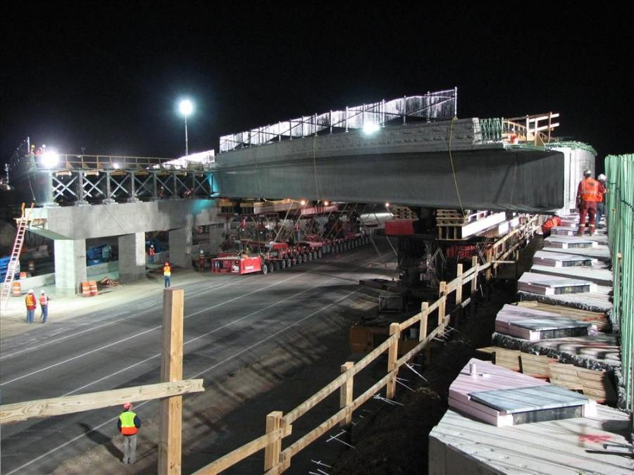 Mobile transporters help set bridge girders in place during critical night time work.