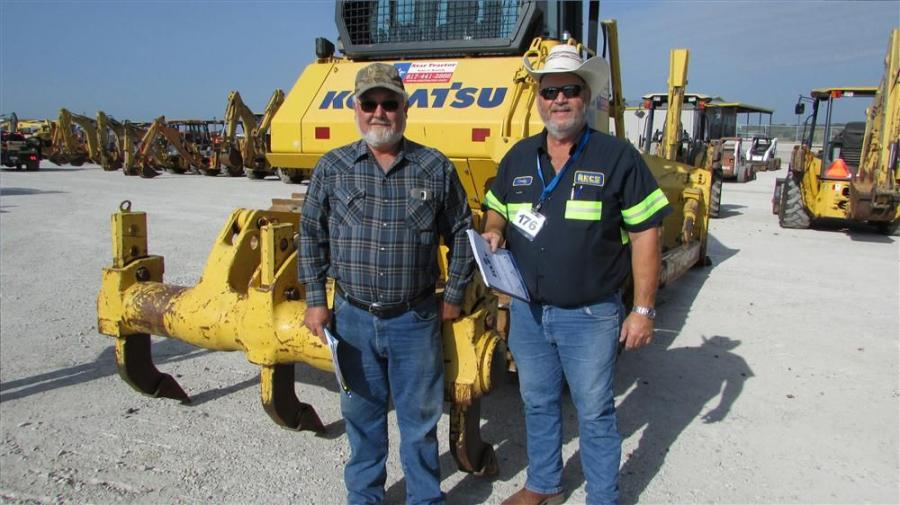 Jimmy Gosdin (L), Gosdin Dozer Service in Glen Rose, Texas, takes a photo op with Corky Underwood, RECS in Prosper, Texas, and this 65EX Komatsu dozer at the Cisco Grand Opening.