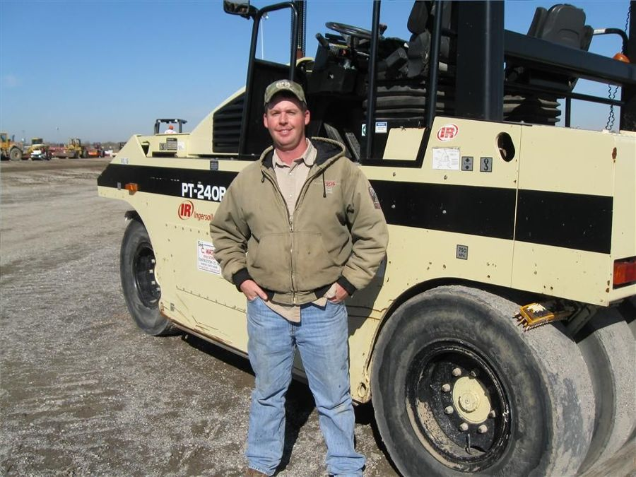 Weslie Scott of WesScott Inc., Cooper, Texas, is all smiles after taking a close look at this Ingersoll Rand PT240R rubber-tired roller.