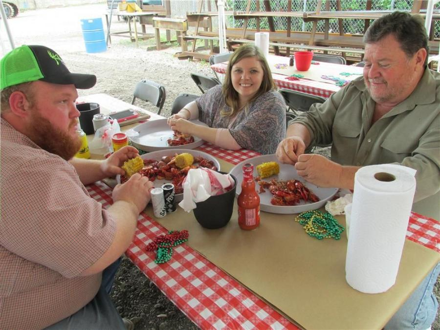Crockett Boney (far L) and his dad, Mike Boney of Jet Underground Utilities in Balch Springs, Texas, have the nice company of Candace Gillespie while making their way through the crawfish.