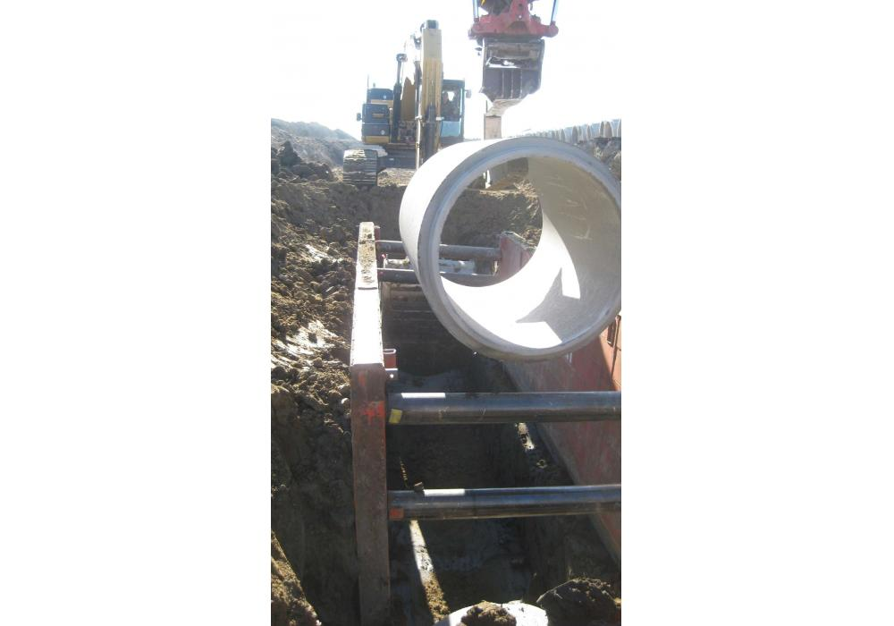 A ramp from the back of the trench box was used to lay the pipe with a custom-built pipe hook that was used with a Rototilt. With each pull of the box, Progressive Structures would lay a pipe, compact it with its modified compactor and push a road forward