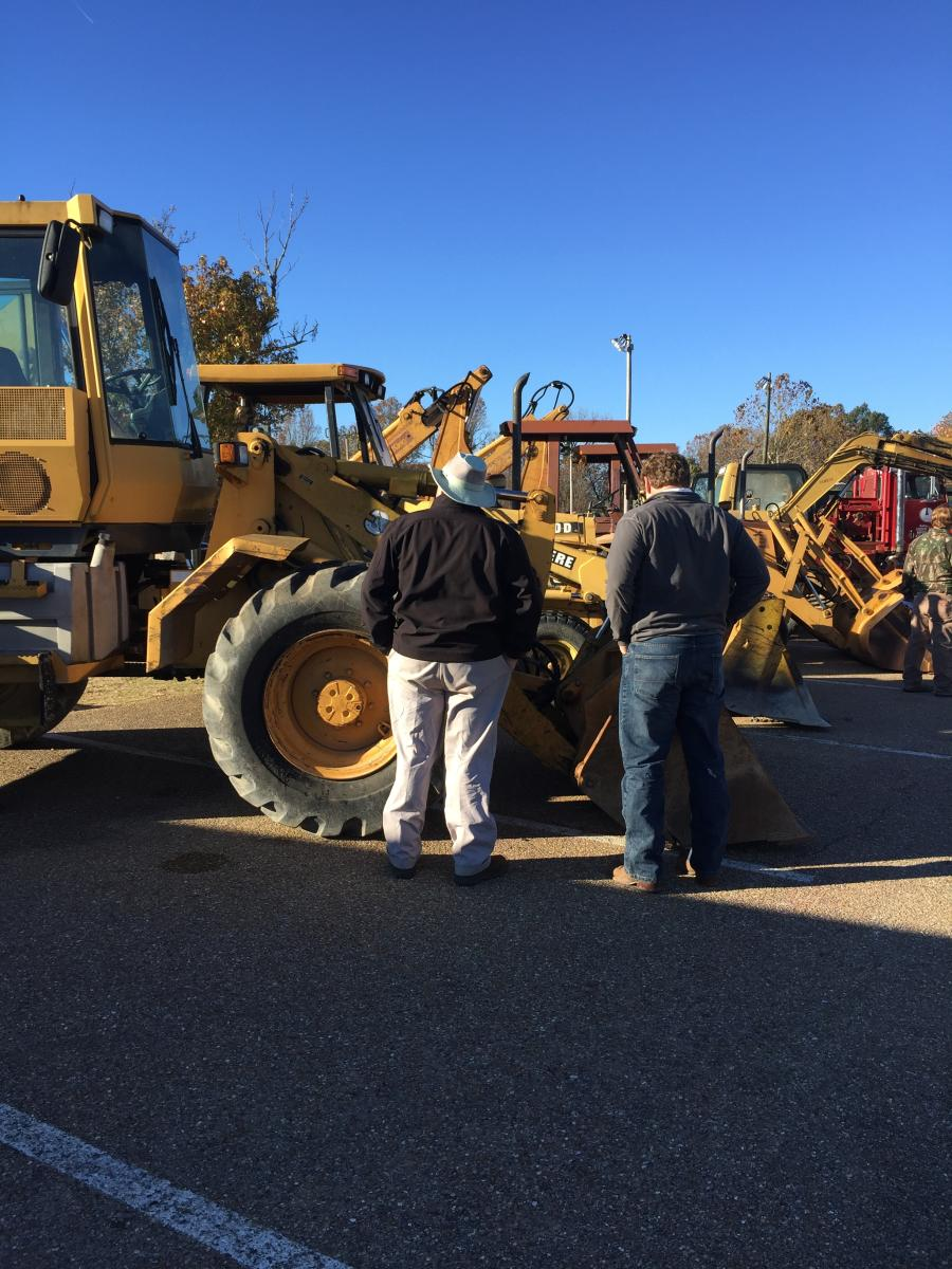 Jeff Martin (L), president, and Patrick Valkenburg, sales representative, examine the John Deere wheel loader up for auction.
