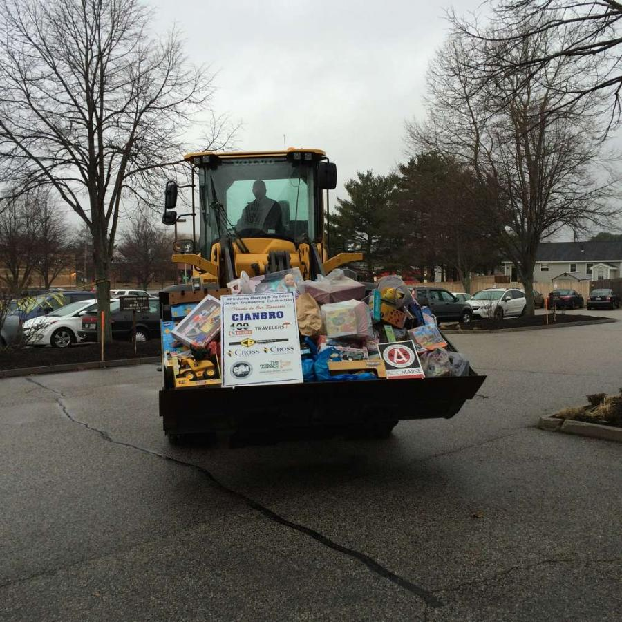 Chadwick-BaRoss salesperson Adam Lampron drove the loader full of toys.