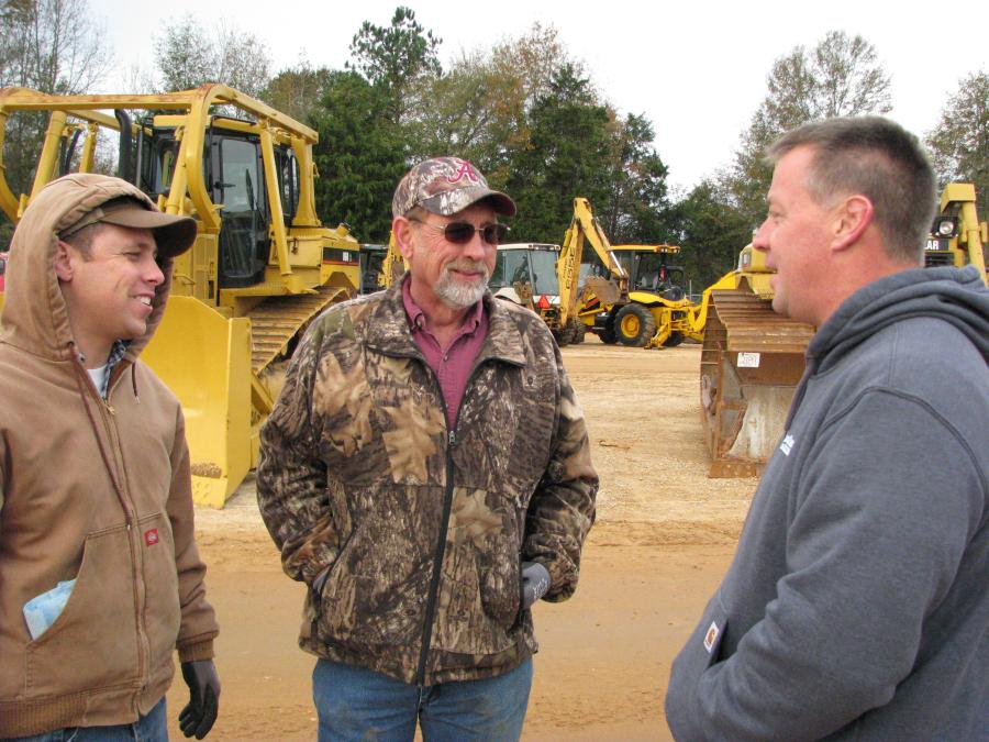 (L-R): Zach and Autrey Burns, both of Kyuka Farms, Attalla, Ala., and Bill Woods of Woods Equipment Company, Nashville, Tenn., talk about the lineup of machines about to go on the auction block on day two of the sale.