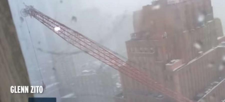 A huge construction crane being lowered to safety in a snow squall plummeted into a Lower Manhattan street Friday, killing a person in a parked car and leaving three people wounded by debris that scattered as the rig's lengthy boom fell.
