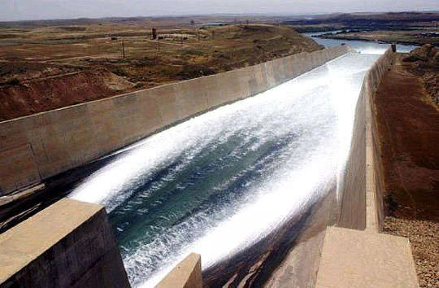 Water rushing out one of the chute spillways at the Mosul Dam. The concrete-lined chute exits to a ski jump section for energy dissipation.