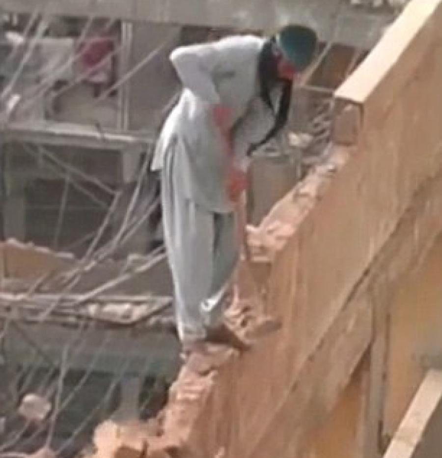 The clip, which was uploaded to Facebook and is believed to have been filmed in the Middle East, shows the unconcerned construction worker taking a mallet to the narrow wall he is standing on.