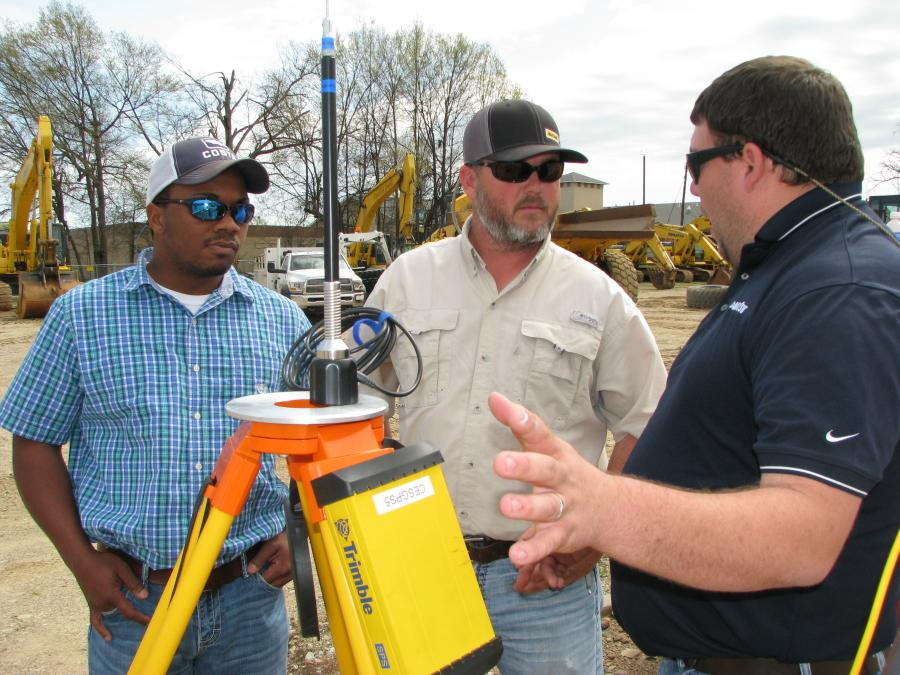 (L-R): Justin Whaley and Wesley Stanton, True North Earthworks, Memphis, Tenn., have a conversation with Anthony Neely, Power Equipment Company, about the various components used in intelligent machine control systems.
