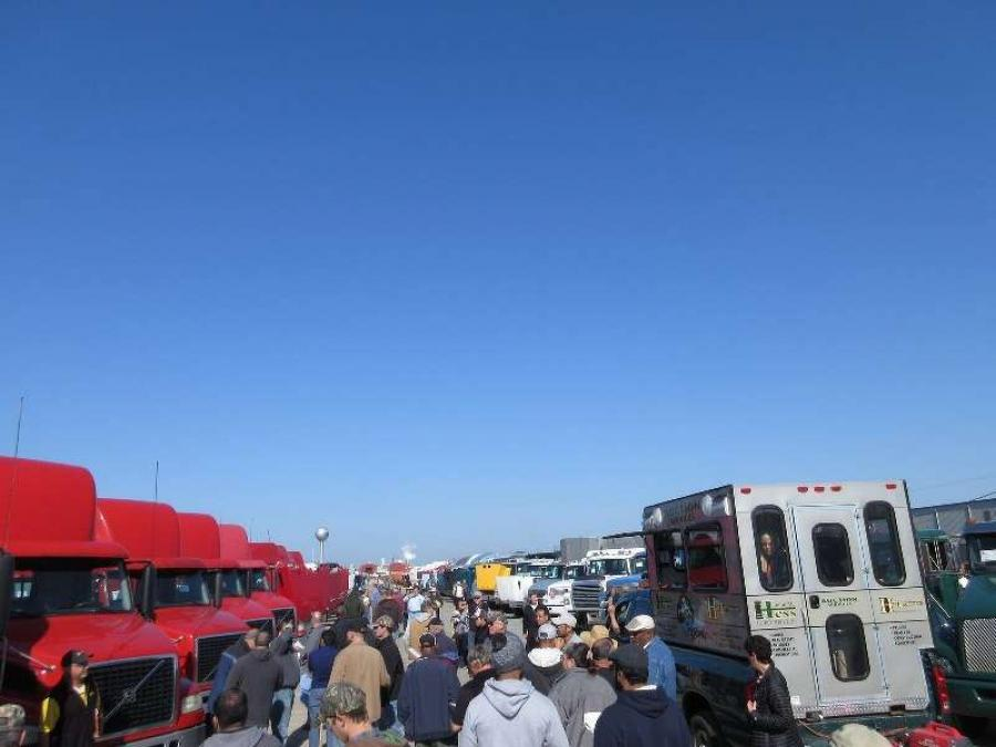 Buyers inspect the selection of trucks for sale on the Hess Auctioneers lot.