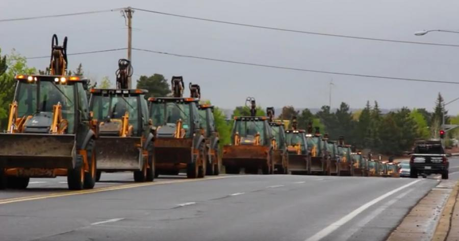 Image courtesy of YouTube.   The event included a procession of more than 30 backhoe loaders.