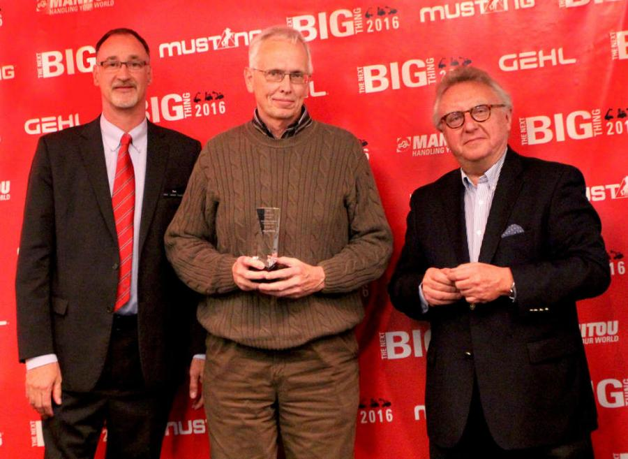 Dan Miller, President & CEO of Manitou Americas, and François Piffard, Executive  VP of Sales and Marketing for Manitou Group, present the 2015 Mustang Top  Dealer Award to Dave Aumiller from Penn Equipment Co.