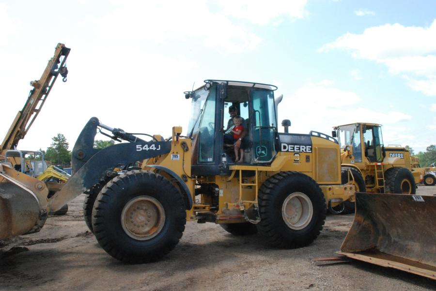 Greg (L) and Trevor Williams, Dirt Inc., inspect the Deere 544J wheel loader during the Saturday auction.""