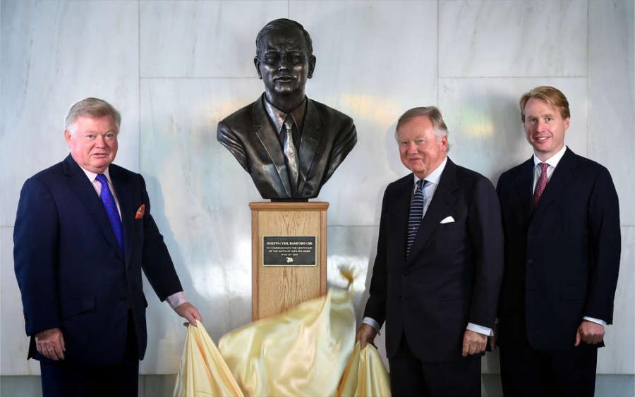 (Left to right) Mr. JCB's sons Mark Bamford and JCB Chairman Lord Bamford and his grandson Jo Bamford, Group MD of Global Accounts, proudly unveil a new bust of Joseph Cyril Bamford, founder of JCB.