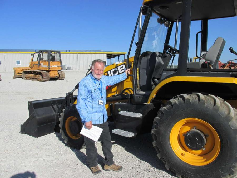 Wayne Copley, Wayne Copley Trucking of Muleshoe, Texas, takes careful measurements of this JCB 3CX loader/backhoe for hauling purposes.
