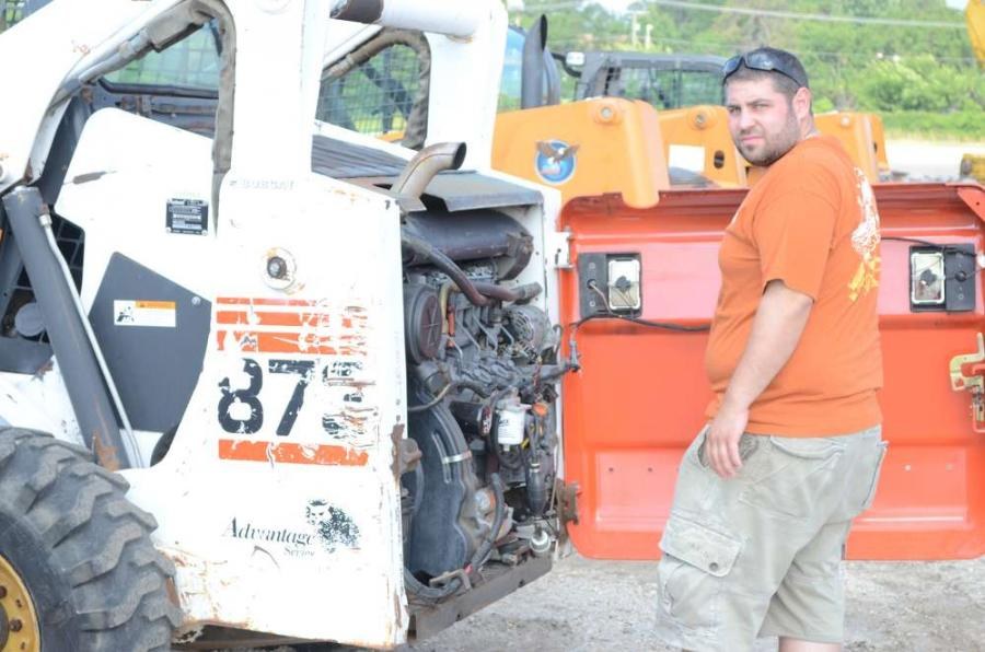 Joe Barros, vice president of Dita Inc., Woodbridge, N.J., checks behind the hood of this Bobcat skid steer.