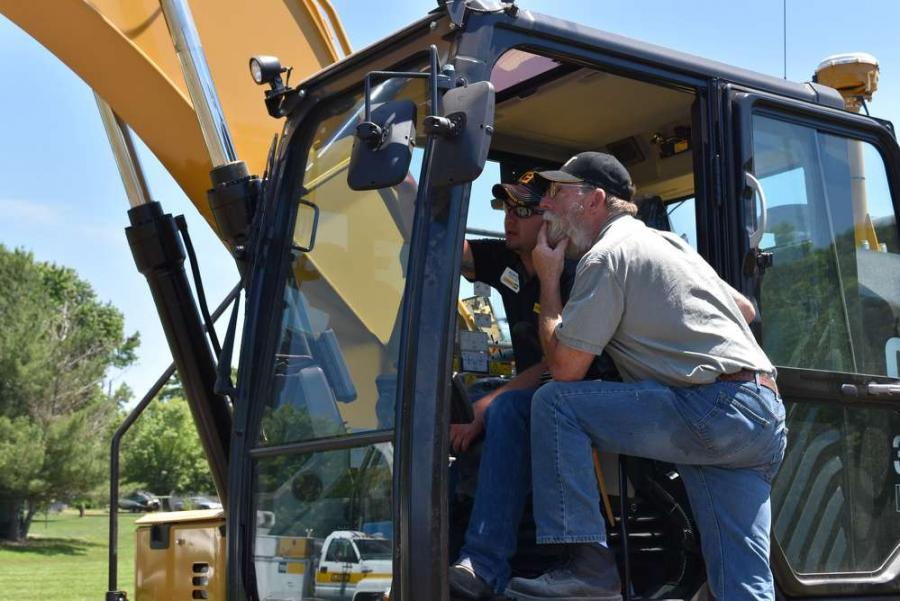 Kenton Parsons (L), Altorfer shop technician, talks about the 323FL hydraulic excavator with an attendee.
