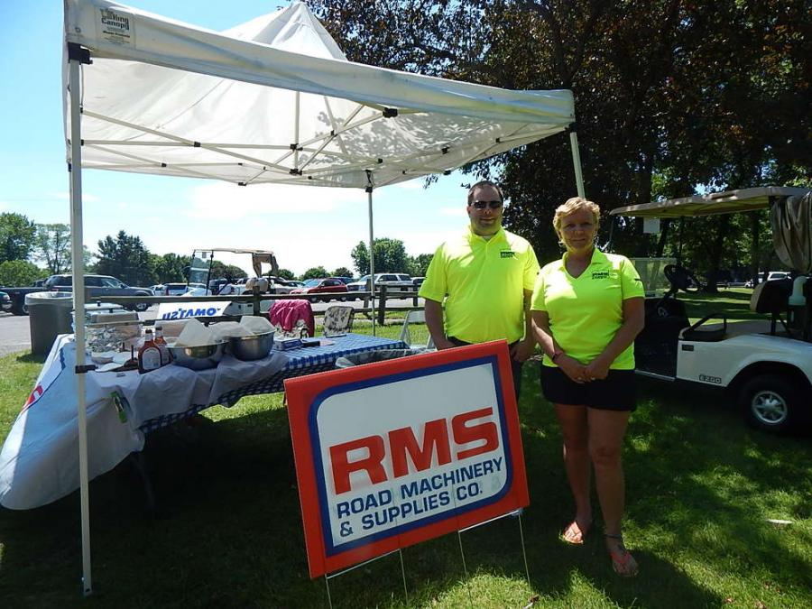 Road Machinery and Supplies, Savage Minn., was voted best food on the course. Karen Montour, rental manager, Savage, Minn., and JJ Bunn, parts manager, Savage, Minn., serve the golfers.