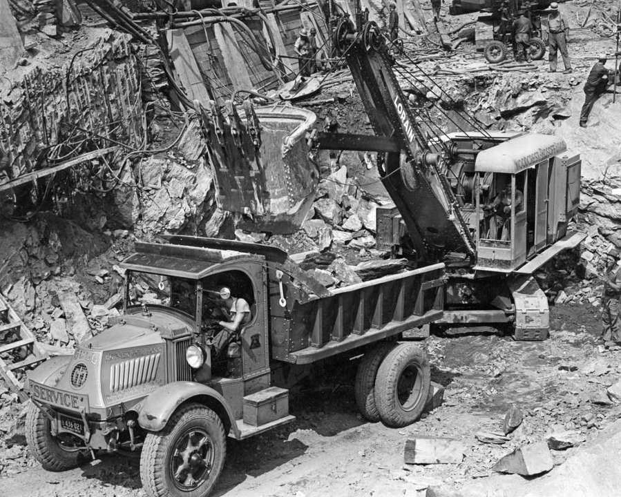 """Edgar Browning Collection photo. A Woodcrest-Rosoff Lorain shovel loads blasted rock into a Mack AC """"Bulldog"""" heavy single axle chain drive dump truck. The truck is owned by the Andrew Gull Corporation of Brooklyn, N.Y. The work depicted is at the East River Tunnel approaches at 1st Avenue and 37th Street in New York City, circa 1937. Wagon drills hammer blast holes on the ledge above."""