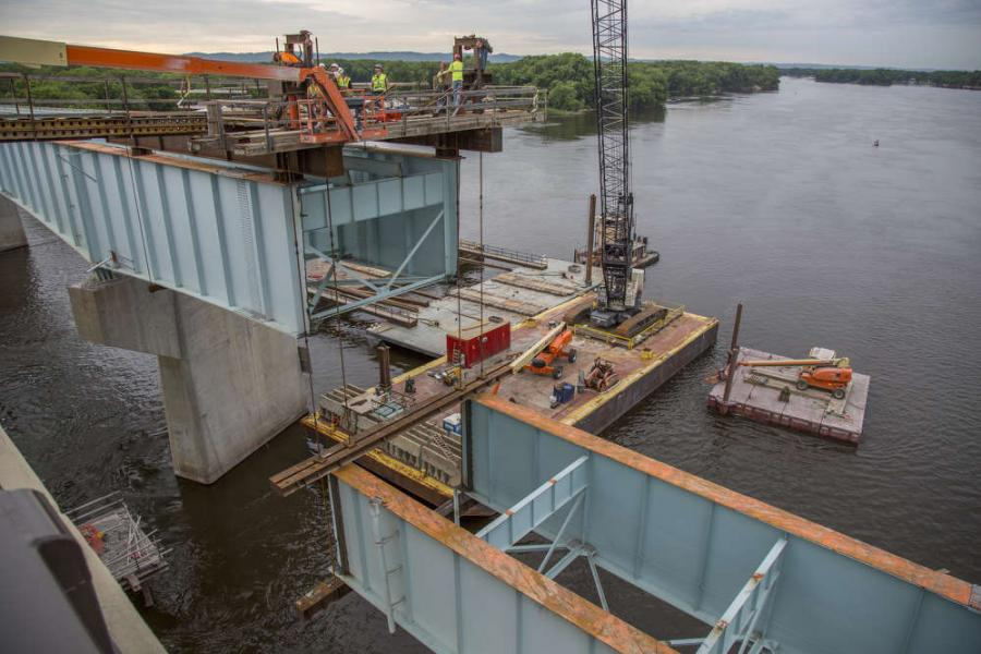 Crews remove sections of the existing bridge and place them onto a barge.