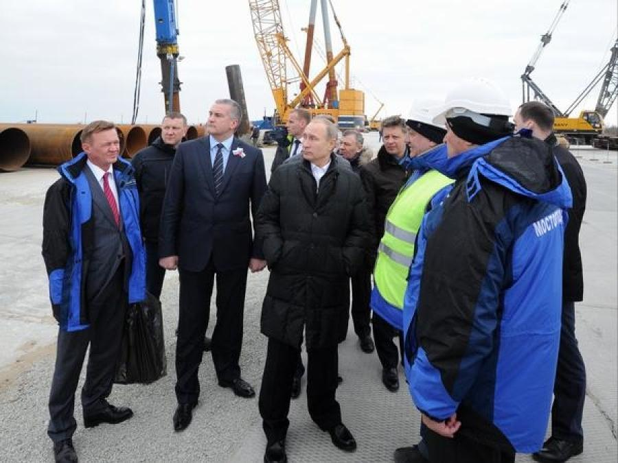Russian President Vladimir Putin (center) joins Russia's federal highway agency head Roman Starovoit (left) and Crimean leader Sergei Aksyonov (second from left) on a visit to the Kerch Strait bridge construction site on Tuzla Island on March 18. The bridge will link Crimea to mainland Russia. ( Mikhail Klimentyev/AP photo)
