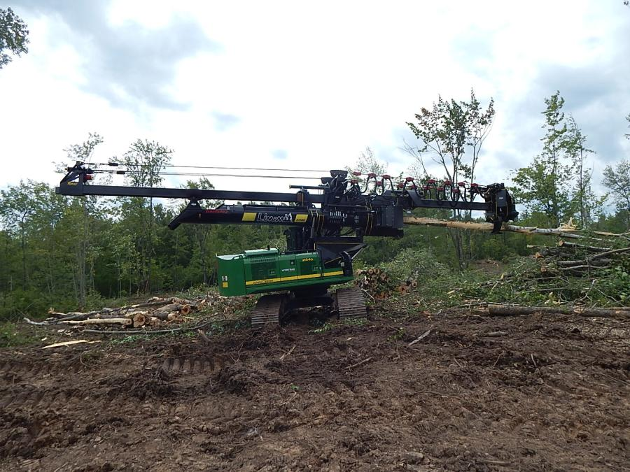 The operator uses a John Deere 2154D logging processor.