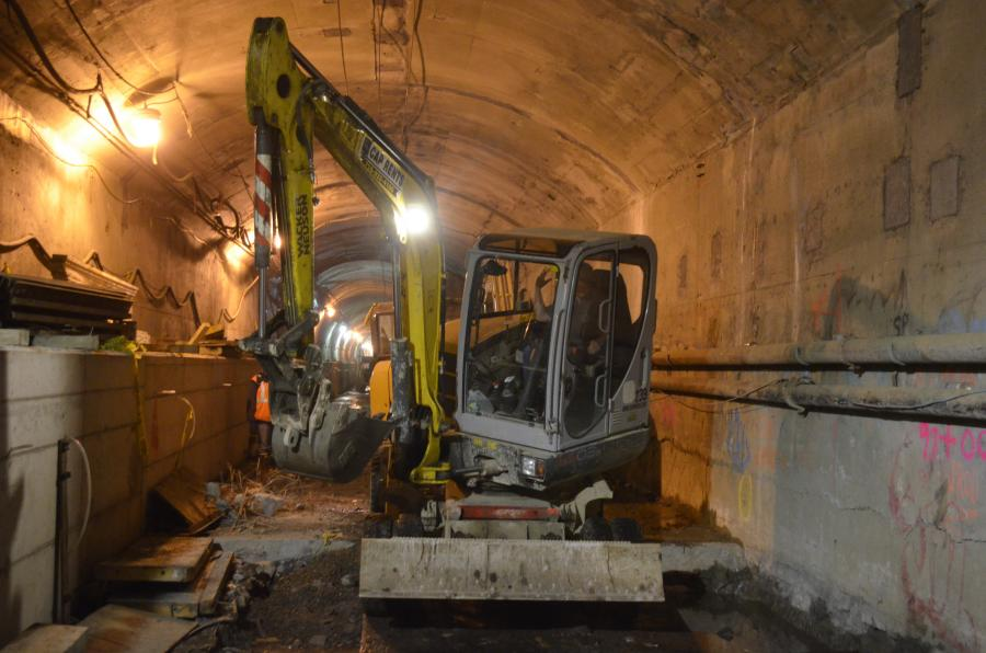 The Wacker Neuson 6503 wheeled excavator cleans up a milled area of the tunnel floor. Due to its unique size and maneuverability, the cab is able to spin 360 degrees — without making contact with the tunnel wall — and head back down the tunnel in the opposite direction.