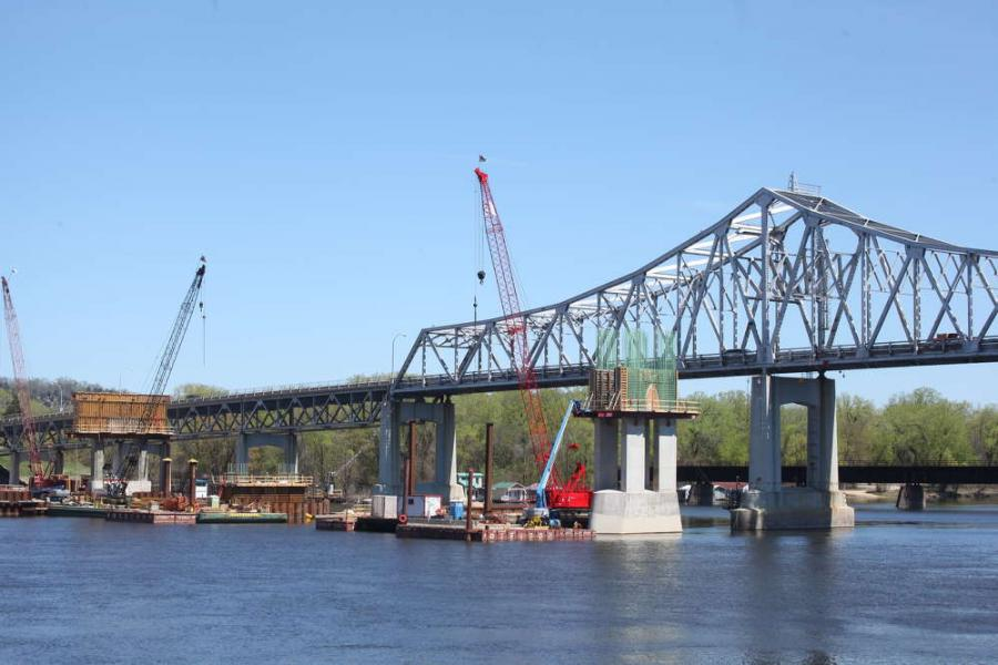 The through truss of the existing bridge, which opened in 1942 and is a historic landmark for the city of Winona, looms above the construction activity on the new bridge piers.