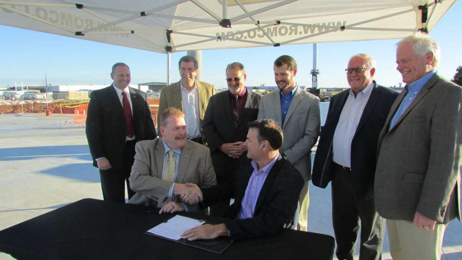 (L-R, sitting): Scott Carnell, president of Atlas Copco, and Robert Mullins, CEO of ROMCO, make it official for ROMCO to distribute Atlas Copco power products. (L-R, standing) are Clint Blair, regional channel manager of Atlas Copco; Craig Burkert, CFO of ROMCO; Alan Kurus, vice president of Atlas Copco; Gable Sprague, ROMCO Power Systems division manager; Charlie Clarkson, president of ROMCO; and David Fitch, division president of ROMCO.