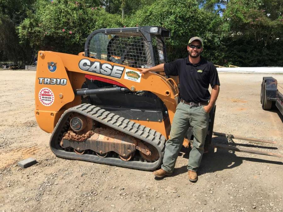 Kody Duke, owner/partner of Precision Landscaping, stands in front of the company's Case TR310 compact track loader.