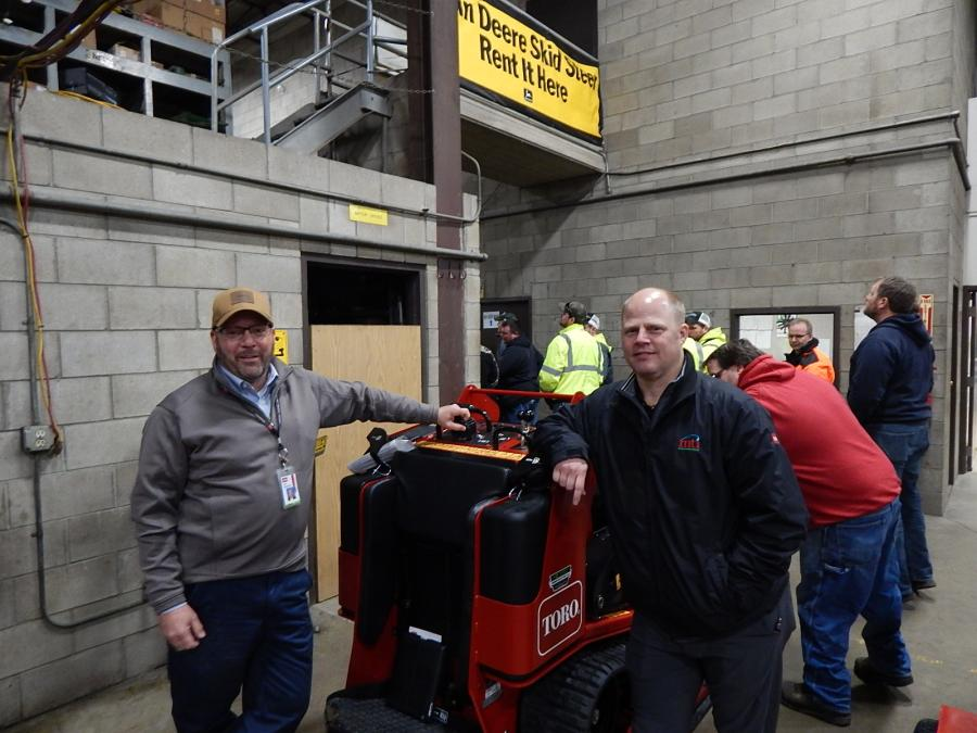 Jon Almquist (L), district sales manager of Toro, Bloomington, Minn., talks with Darren Droegemueller, MTI Distributing, outside sales representative, about this Toro TX-1000 wide track dingo.