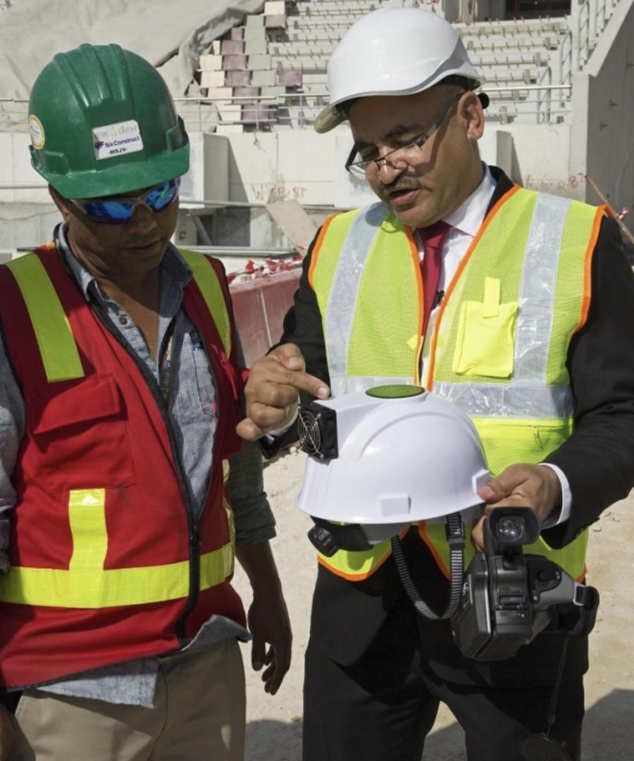 "Dr. Saud Abdul-Aziz Abdul-Ghani, of Qatar University, demonstrates the ""air conditioned"" hard hat (Supreme Committee for Delivery & Legacy)"