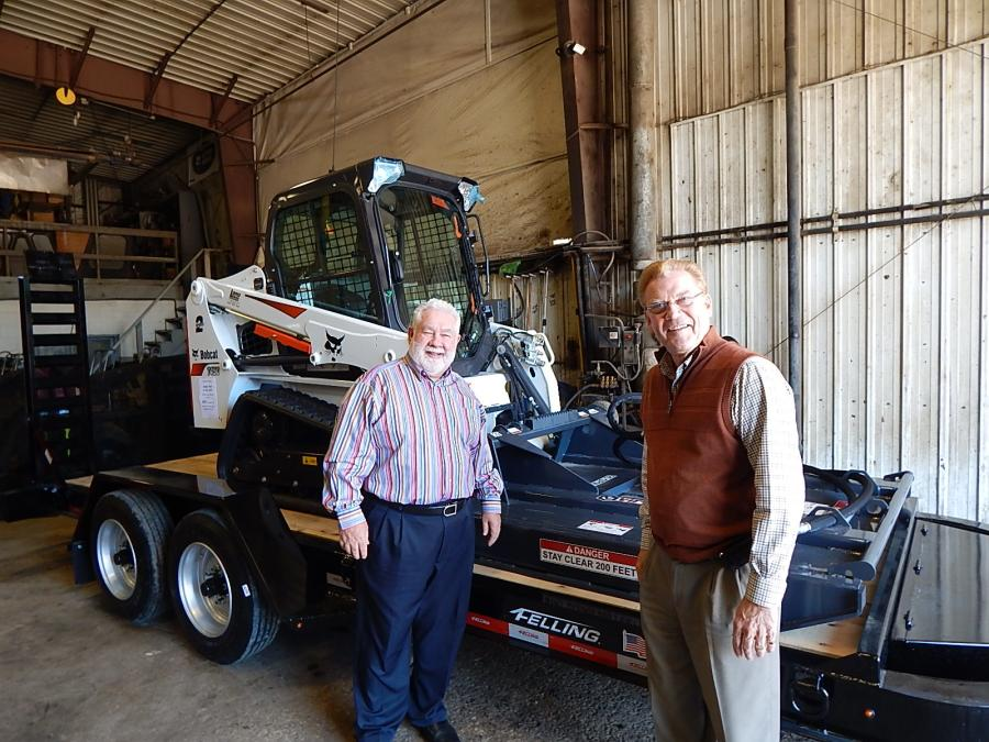 Joe Lano (L), sales manager of Lano of Shakopee, talks with Merle Felling, founder of Felling Trailer, Sauk Centre, Minn., in front of a Bobcat T450 track machine with a Bobcat brush mower and a Felling skid steer trailer.