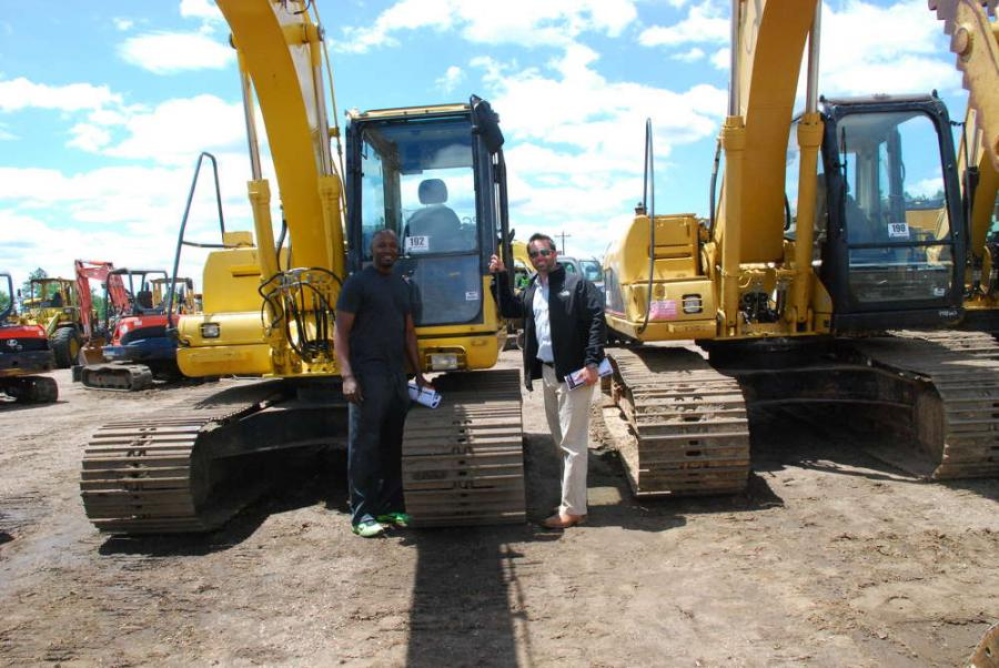Jude (L) and Joey from Gulfport, Miss., stand with a 2008 Komatsu PC130-8 hydraulic excavator.