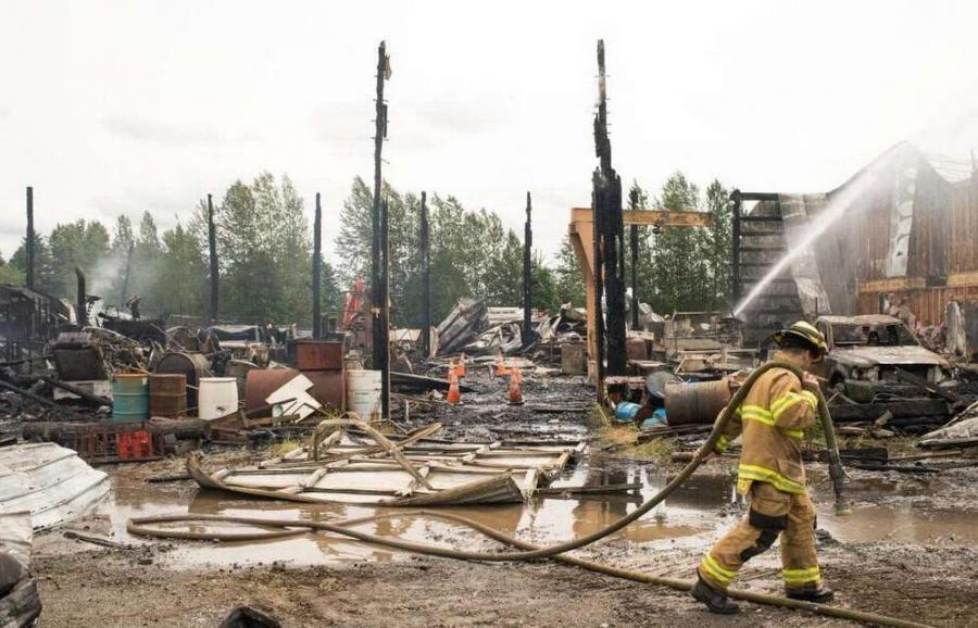 Firefighters from Whatcom County Fire District 7 work to put out remaining hot spots during a fire at Friberg Construction on Saturday, June 17, in Ferndale.