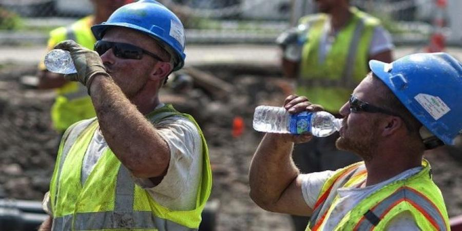 Workers in hard hats and vests labored in the heat and try to stay hydrated.