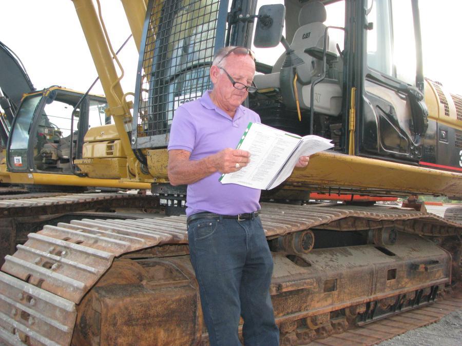 Bob Wigington of Wigington Contractors, Jasper, Ga., reads up on the excavators in the sale.
