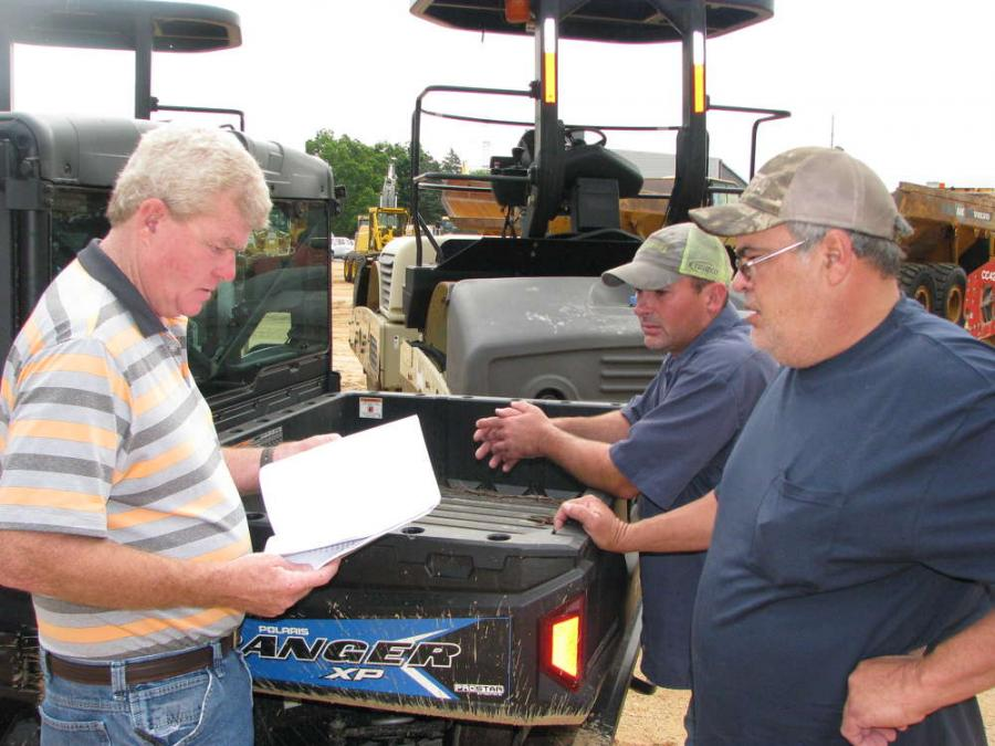 (L-R): Olen and Obie Burrage and Brad Permenter of Southern Trucks & Equipment, Philadelphia, Miss., talk about the equipment up for bid.
