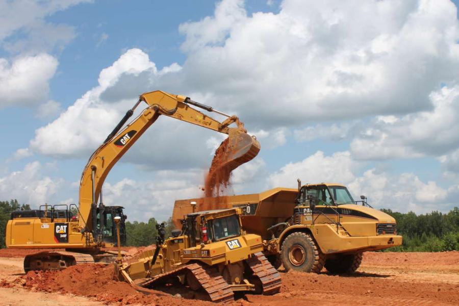 The operator of a Cat 349F excavator loading dirt into a Cat articulated truck while a small Cat D6T dozer moves in foreground on a long straight grade.