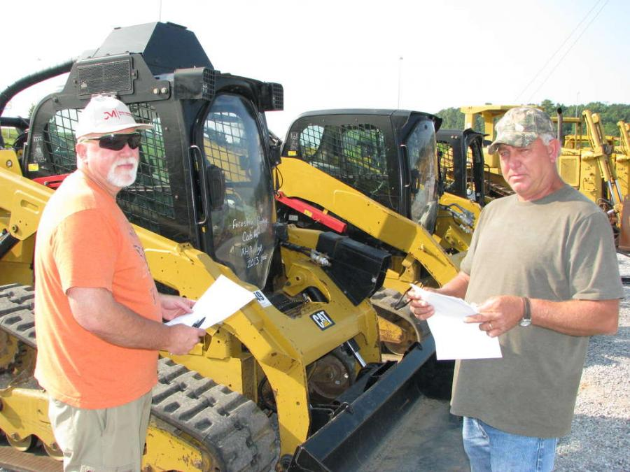 Bruce Lowery (L) of Lowery Properties, Arley, Ala., and Ricky Frazier of R&S Roofing, Ardmore, Ala., look over some of the compact track loaders for sale.