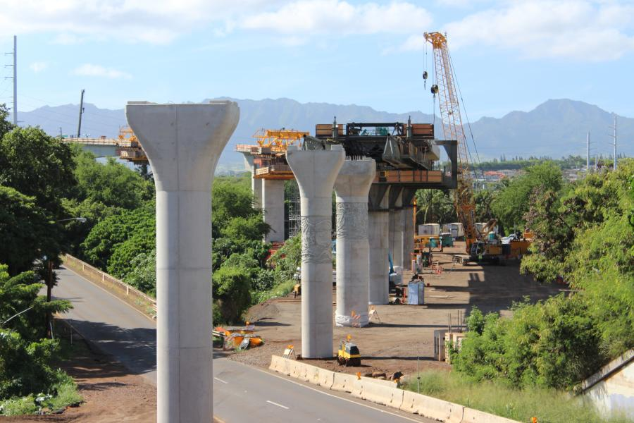 Train tracks supported by concrete pillars snake through Oahu neighborhoods and across its lush scenery, ending abruptly in an empty, overgrown field. They're part of a planned $9.5 billion rail transit project — one of the most expensive per capita in the United States.