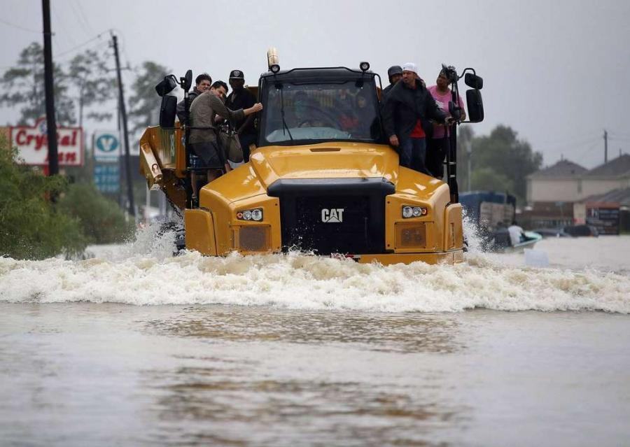 People catch a ride on a Caterpillar 745C articulated truck down a flooded street as they evacuate their homes after the area was inundated with flooding from Hurricane Harvey on Aug. 28 in Houston, Texas. See page 54 for more.