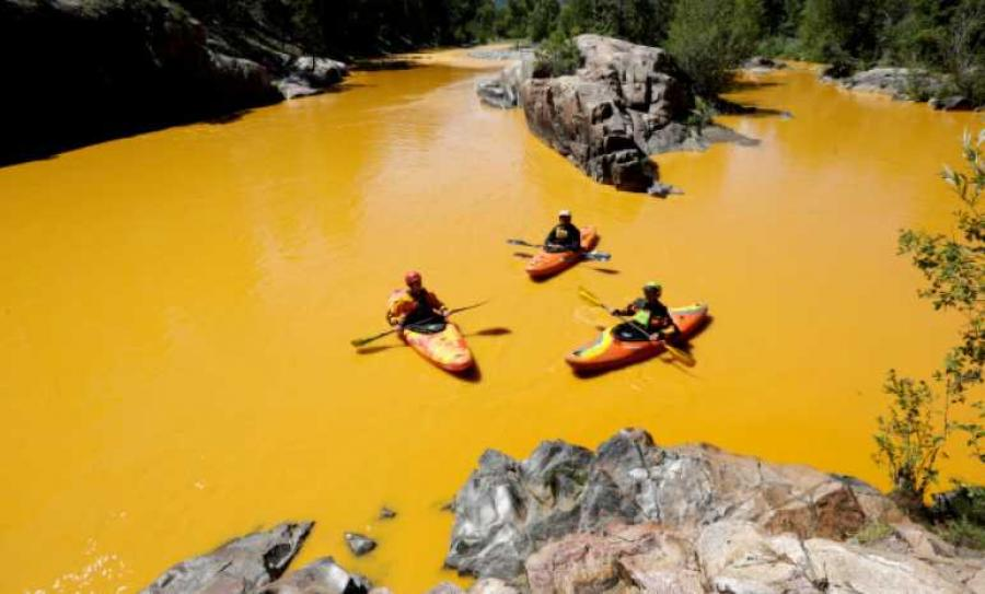 People kayak in water colored from the mine waste spill. 